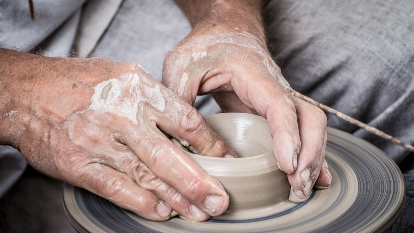 Potters hands throwing a pot on the wheel.